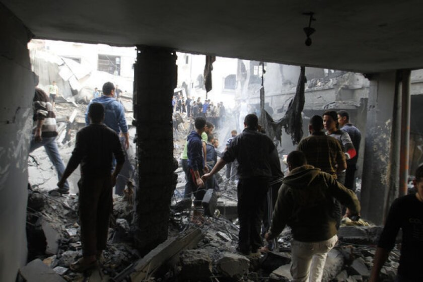 Palestinians stand in the rubble of the Dalu family's house in Gaza after an Israeli air strike. Ten members of the family -- six women and four children -- were killed in the strike, which a new report from Israel's military says was a mistake.