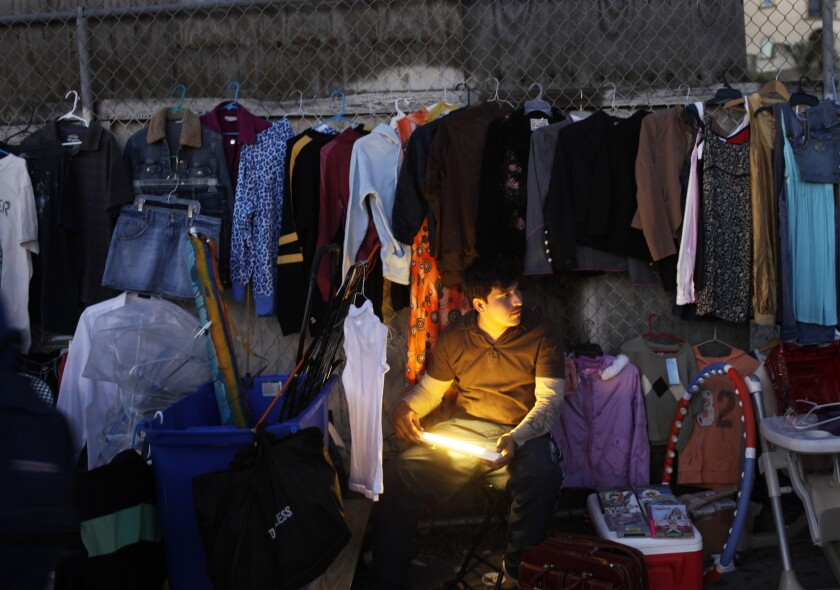 A clothes vendor illuminates his makeshift shop along 6th Street in the Westlake district of Los Angeles on Nov. 26, 2011.