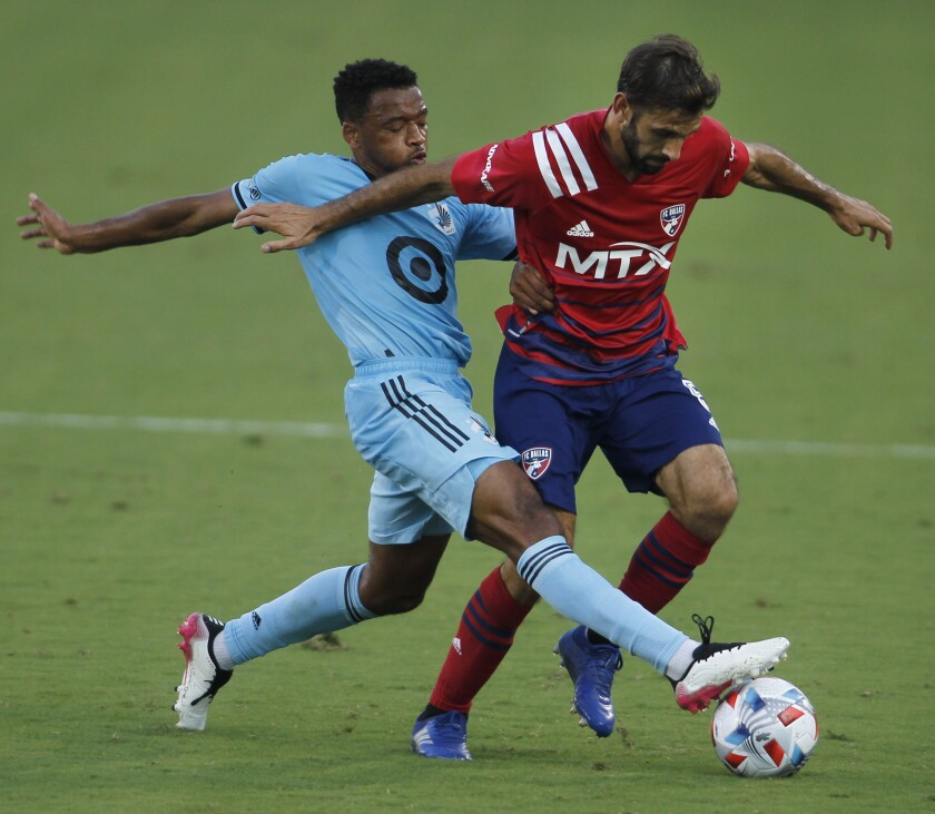 FC Dallas midfielder Facundo Quignon, right, tries to maintain ball control as Minnesota United midfielder Jacon Hayes defends during the first half of an MLS soccer match in Frisco, Texas, Saturday, June 19, 2021. (Steve Hamm/The Dallas Morning News via AP)