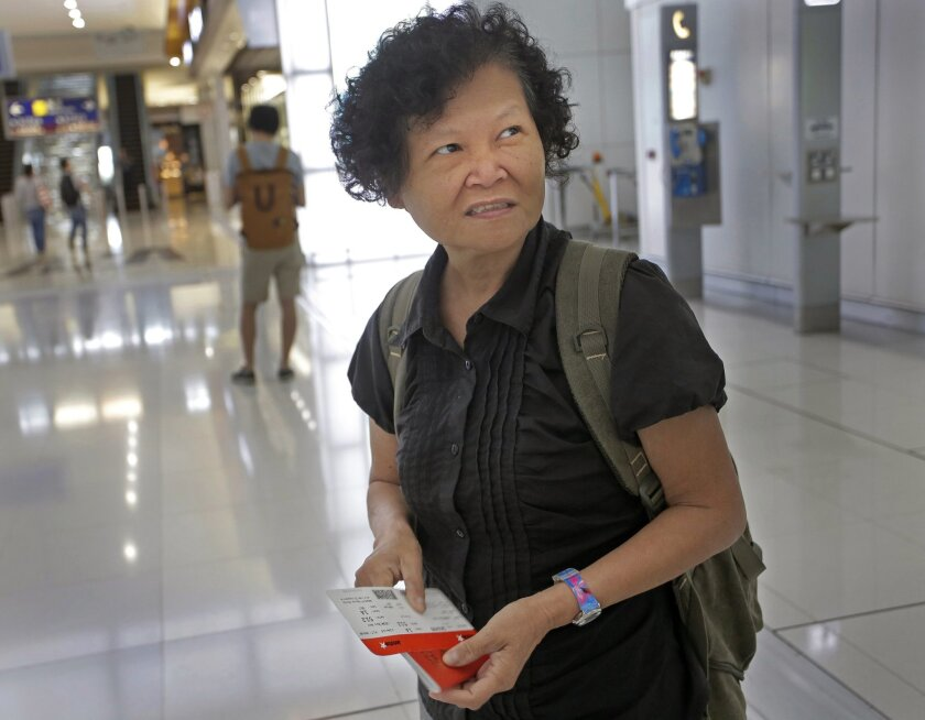 Mary Seow holds a boarding pass after she checked in with her son, in the background carrying a backpack, at the airport in Hong Kong, Saturday, Nov. 21, 2015. Seow, a Singaporean woman who went missing nearly five years ago, has been reunited with her son after her plight was reported in an Associated Press story about people who sleep at 24-hour McDonald's outlets in Hong Kong. (AP Photo/Vincent Yu)