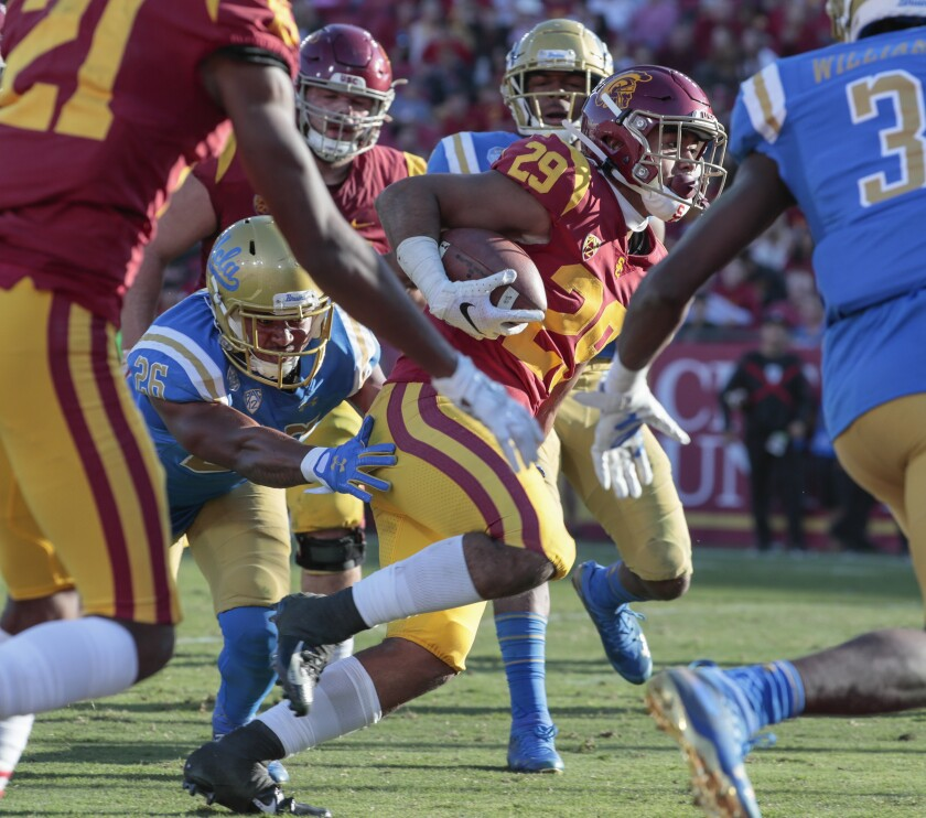 USC running back Vavae Malepeai (29) eludes the tackle of UCLA linebacker Leni Toailoa (26) for a touchdown run in the third quarter at the Coliseum on Saturday.