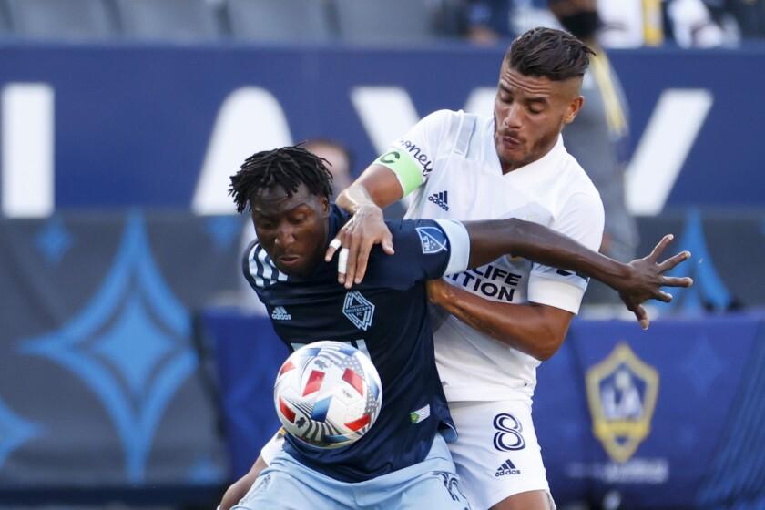Galaxy midfielder Jonathan dos Santos and Vancouver Whitecaps midfielder Janio Bikel fight for the ball