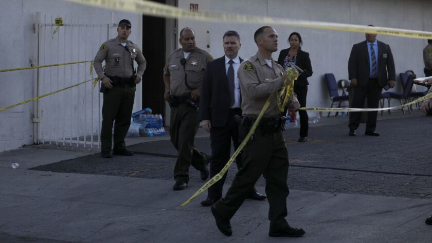 A Los Angeles County sheriff's deputy removes tape from the parking lot entrance outside the church in Compton.