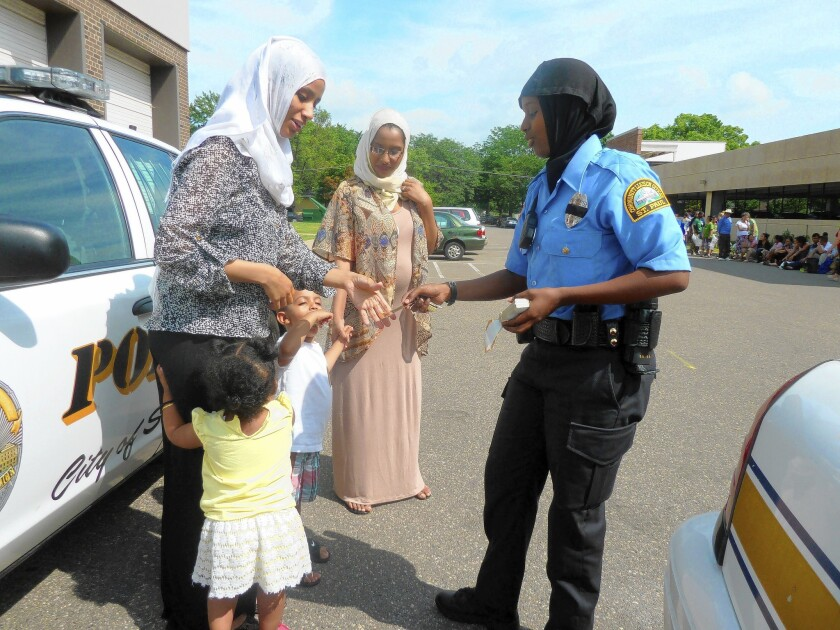 Kadra Mohamed hands out police badge stickers at a community event attended by Somali families. Mohamed is a community liaison officer in St. Paul, Minn., the first Somali woman on the city's police force.