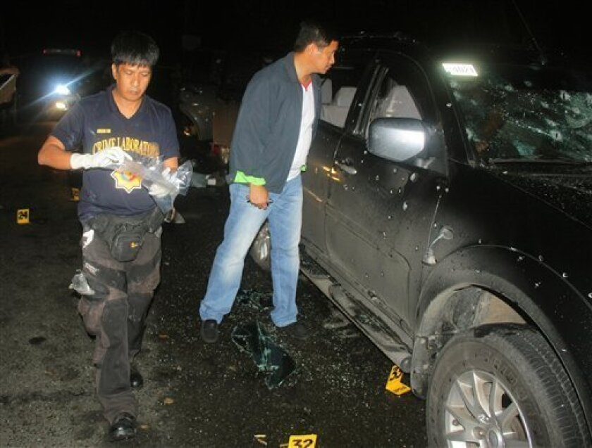 UPDATES CAPTION INFORMATION - FILE - In this Jan. 6, 2013 file photo released by the Philippine National Police Quezon Provincial Director's Office, Quezon provincial police chief Valeriano de Leon, right, looks at a bullet-riddled vehicle at a checkpoint along a road in the town of Atimonan in Quezon province, southeast of Manila, Philippines. Security personnel originally claimed the incident as a shootout with suspected criminals, but the Philippine justice secretary said Wednesday, March 7,