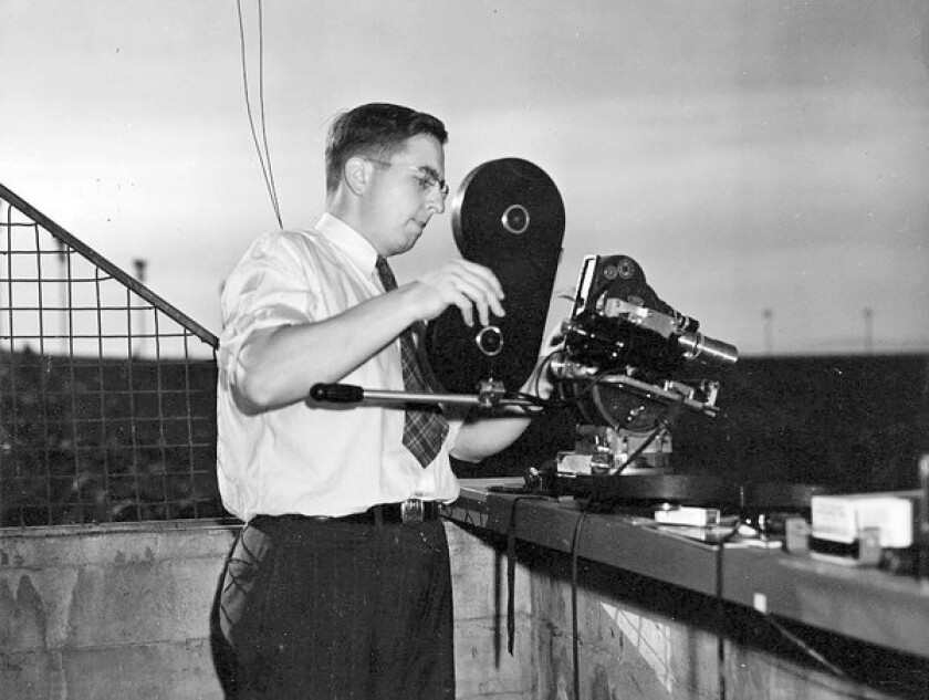 Herb Farmer prepares to shoot a USC football game in 1942, the year he taught his first class at the university.