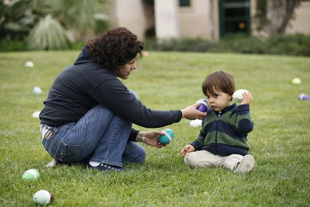 Rosario Sanchez helps Mason Lopes, 2, who is visually impaired, find beeping Easter eggs at Newport Dunes Waterfront Resort on Tuesday. Lopes is one of approximately 50 visually impaired kids at the Blind Children's Learning Center in Santa Ana to participate in the events.