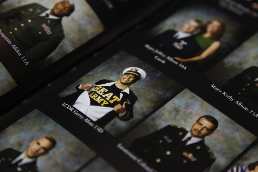 Lt. Cmdr. Gery Alota (center) shows off his Midshipmen pride in an all-Army school yearbook. Alota will be celebrating the annual Army-Navy game along with several other Academy grads on December 14 at Randy Jones All-American Sports Grill.