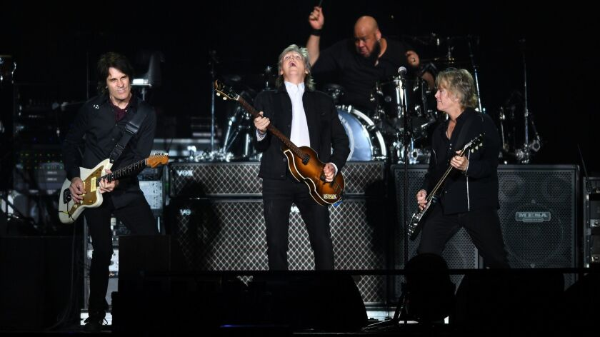 Paul McCartney, center, performs with his band to a sold-out crowd at Dodger Stadium Saturday.