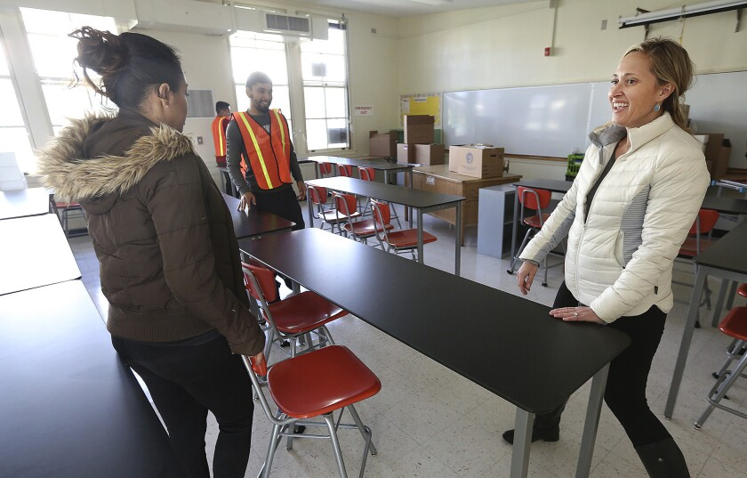 Porter Ranch Community School science teacher Rosie Van Zyl moves tables into position with the help of other LAUSD employees in her new classroom at Northridge Middle School.