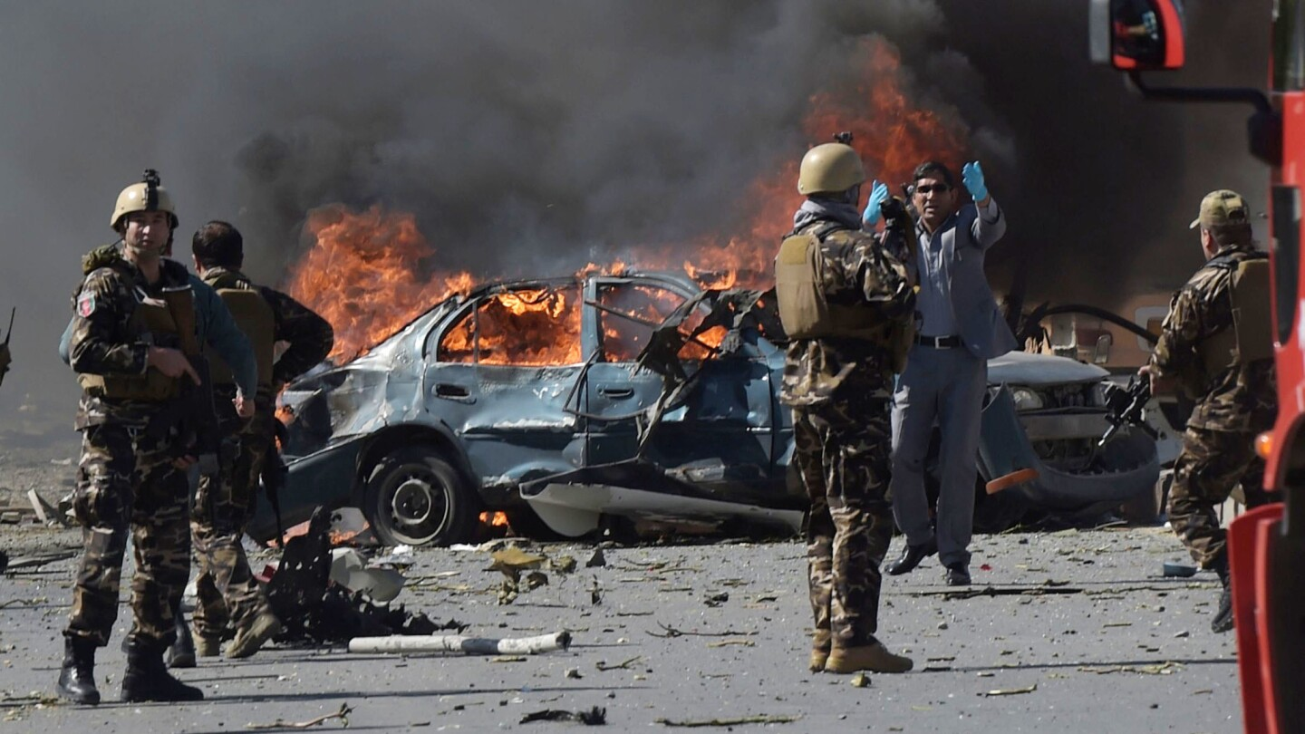 Afghan soldiers keep watch amid burning wreckage and debris after a car bomb exploded in Kabul on Wednesday morning.