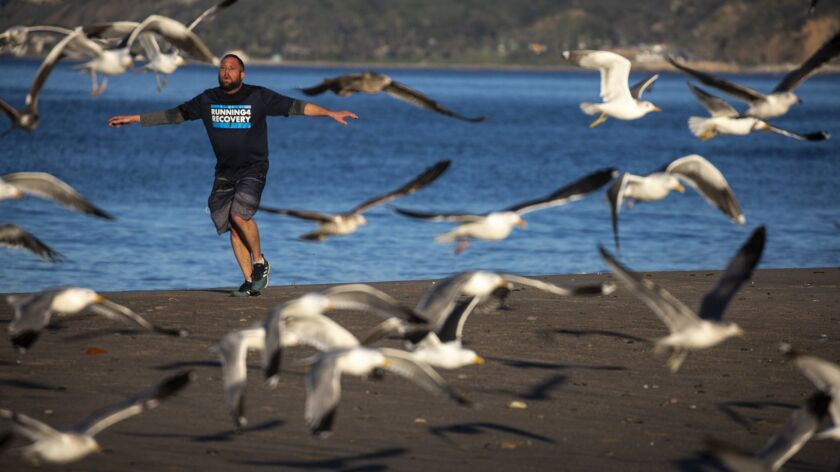 SANTA MONICA, CALIF. - MARCH 16: With outstretched arms, Jeremiah Snyder, 34, of San Diego, runs alo