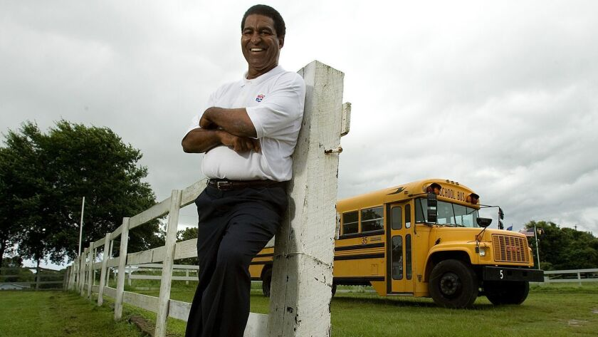 Former Rams linebacker Isiah Robertson poses in front of a fence and a school bus at his Texas rehab center in 2007