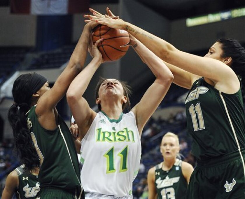 Notre Dame's Natalie Achonwa, center, is fouled by South Florida's Courtney Williams left, as Caitlin Rowe, right, defends in the first half of an NCAA college basketball game in the quarterfinals of the Big East Conference women's tournament in Hartford, Conn. Sunday, March 10, 2013. (AP Photo/Jessica Hill)