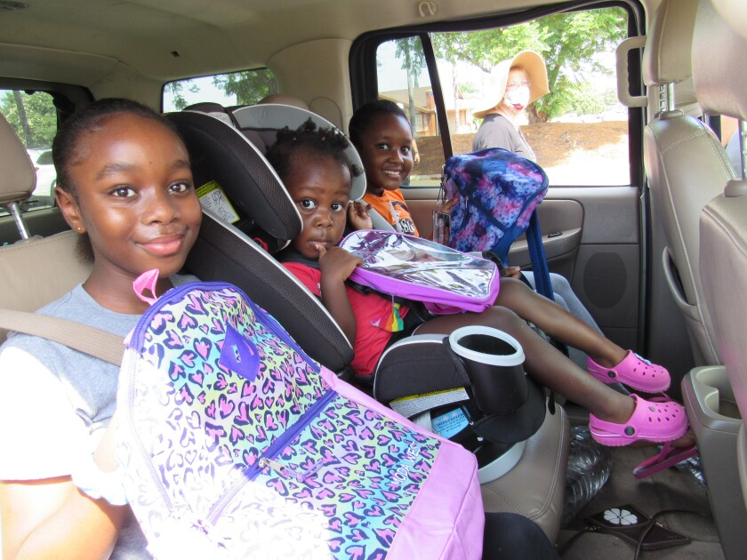 Chet F. Harritt School students, sisters Mercy, Grace and Hope Kamau, got donated back-to-school items in Santee.