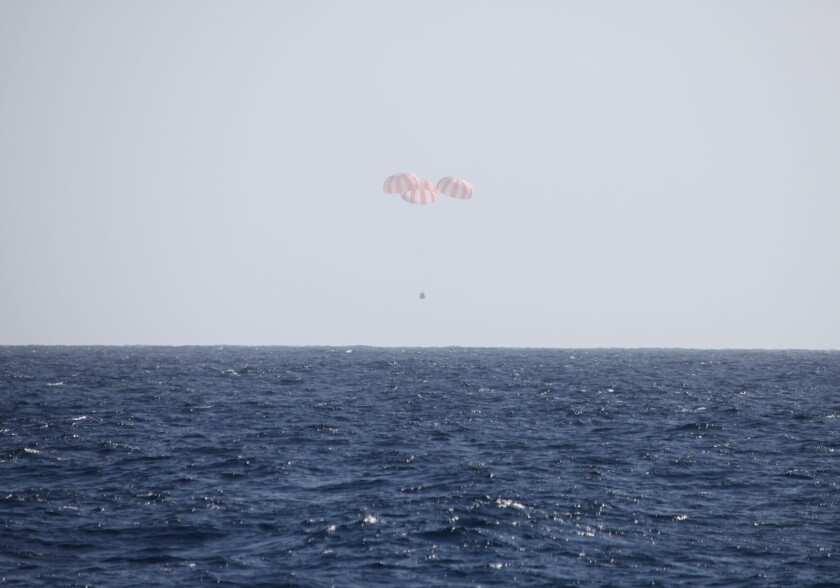 SpaceX's Dragon capsule is slowed by three main parachutes prior to splashdown in the Pacific Ocean.