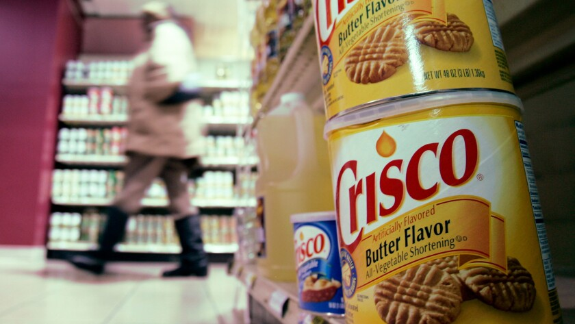 Consumption of vegetable oils, which were invented in the early 1900s, exploded during the 20th century. Above, a shopper walks past an aisle featuring Crisco products in a grocery store in Cleveland, Ohio in 2007.