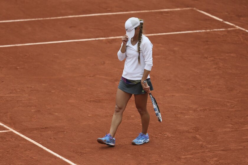 Kazakhstan's Yulia Putintseva covers her face at the end of the second set of the quarterfinal match of the French Open tennis tournament against Serena Williams of the U.S. at the Roland Garros stadium in Paris, France, Thursday, June 2, 2016. (AP Photo/David Vincent)
