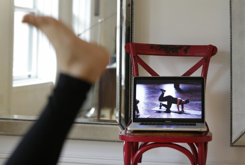 In this April 14, 2015 photo, Christina Macchiarola demonstrates how she uses the Crunch Live fitness app to work out in her apartment in New York. Crunch Live includes many of the workouts that earned the brand a devoted following and have been retired from their brick and mortar gyms.  (AP Photo/