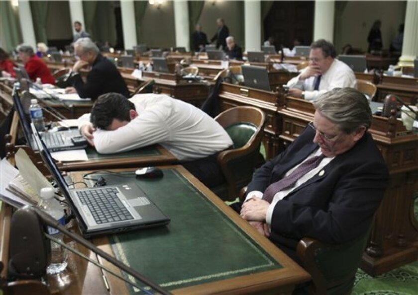 Assembly members Hector De La Torre, D-South Gate,  left, and  Bill Monning, D-Monterey, right, sleep at their desk during an all-night lock down of the Assembly at the Capitol in Sacramento, Calif., Sunday, Feb. 15, 2009.  In an effort to get a budget deal, Assembly Speaker Karen Bass, D-Los Angel