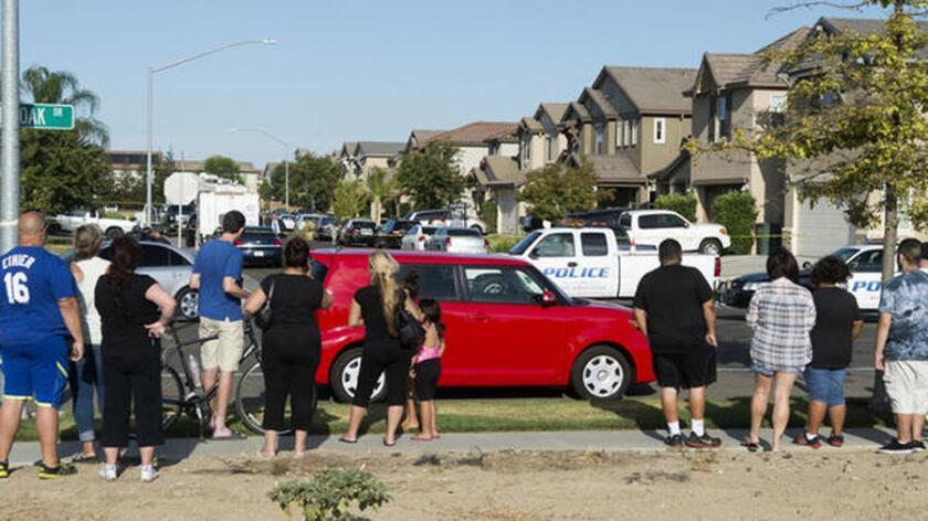 Algunos vecinos de las víctimas se reunieron cerca del hogar donde los cuerpos de cinco mujeres, tres ninas y tres adultas fueron encontrados sin vida en Modesto, en el centro de California.