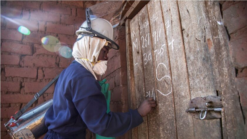 Emely Mwale, 23, who earns $6 a day spraying homes with insecticide in the Katete District of Zambia's Eastern Province, marks the door of a house she has just finished spraying.