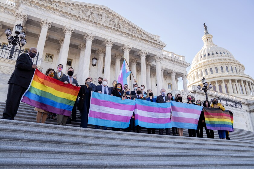 Members of the House of Representatives hold LBGT and transgender pride flags outside the U.S. Capitol in Washington