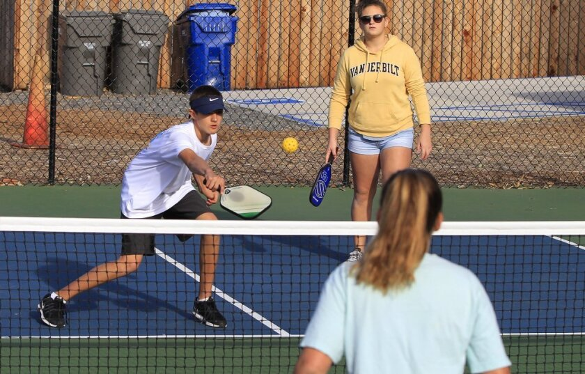 Richard Tanaka, 14, (left) and Kyra Allison, 14, (right) play pickle ball at the Youth Pickleball Tournament at St. Michael's by the Sea on Tuesday in Carlsbad. Foreground is Paige Hansen, 12.