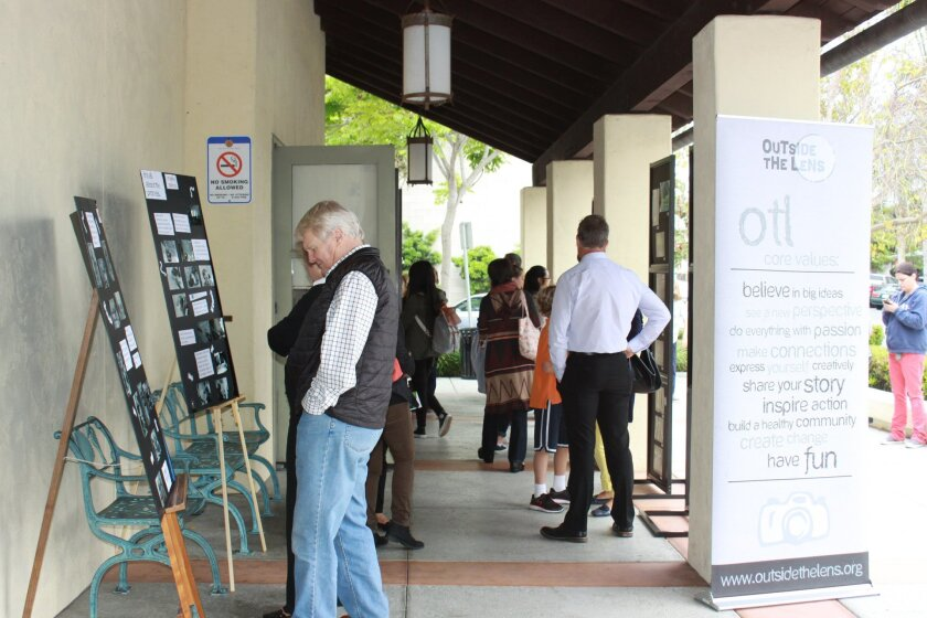 Families, friends and passers by view the images on display in front of the library. The photos will be moved inside, where they will be on display through the summer.