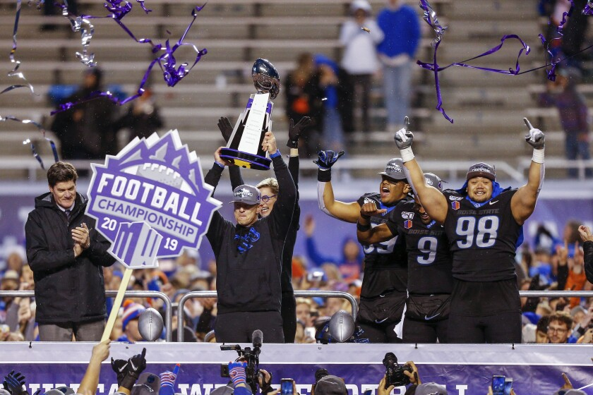 Boise State coach Bryan Harsin holds up the Mountain West Championship trophy.