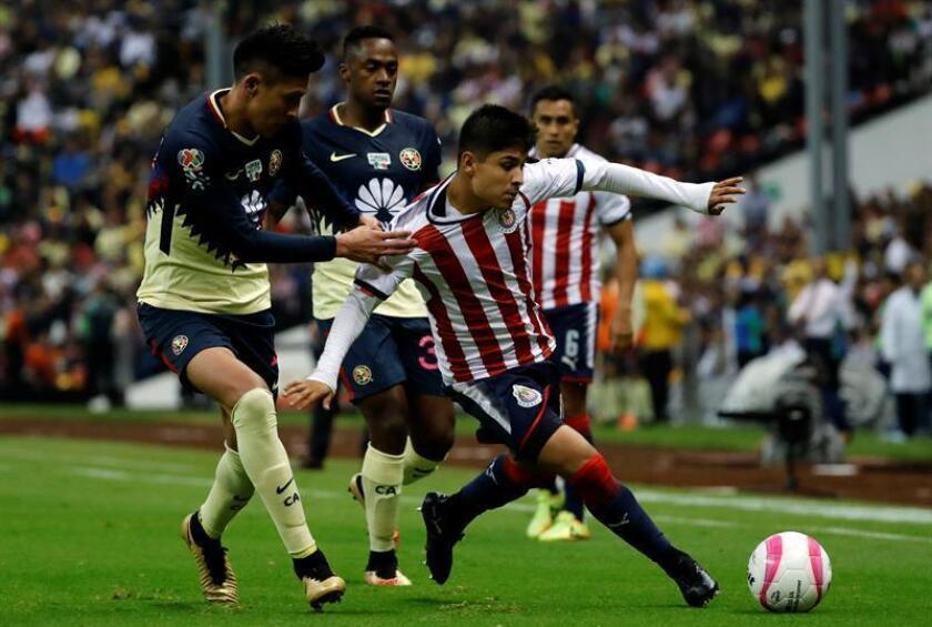 El jugador de América Edson Álvarez (i) y Javier López (d) de Chivas disputan el balón durante un encuentro celebrado en el estadio Azteca. EFE/Archivo