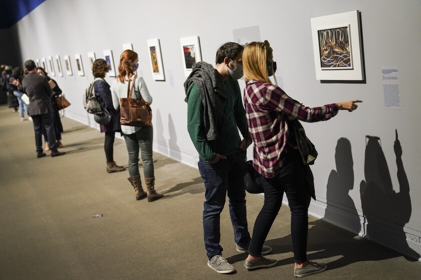 "Visitors wearing protective masks observe COVID-19 prevention protocols as they browse the ""Jacob Lawrence: The American Struggle"" exhibition at the Metropolitan Museum of Art, Saturday, Oct. 17, 2020, in New York. (AP Photo/John Minchillo)"