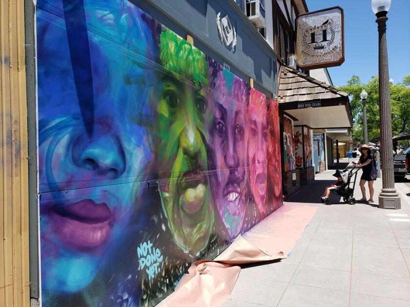 Bright murals along La Mesa Boulevard cover up many windows that had been compromised last month.