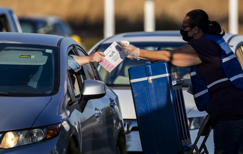 A voter hands her ballot to an election official to be dropped in a ballot box on Oct. 30 in Riverside.