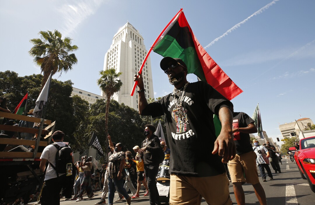 A crowd marched down Spring Street past city hall during a rally to honor George Floyd on the anniversary of his death.