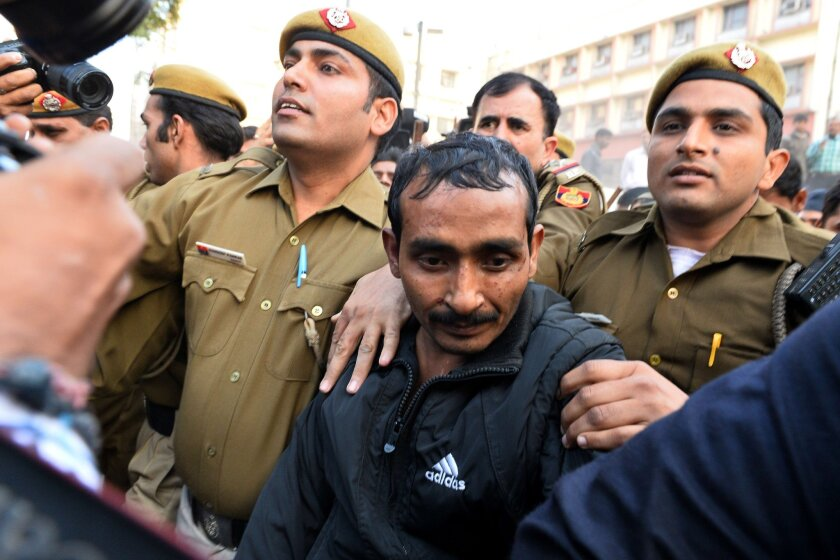 Indian police escort Uber taxi driver Shiv Kumar Yadav, in a dark Adidas jacket, following his court appearance in New Delhi on rape charges.