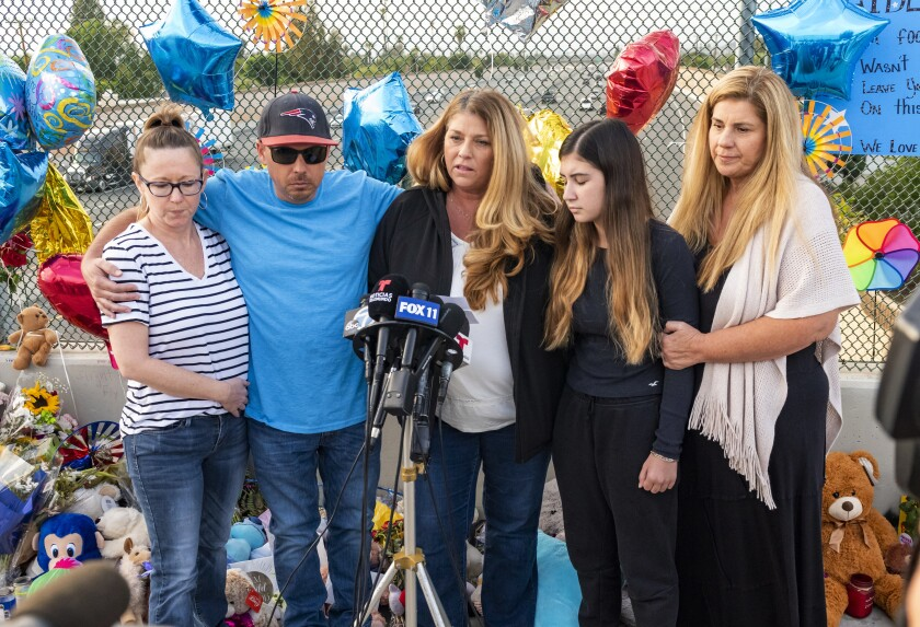 Family members of 6-year-old Aiden Leos stand at a makeshift memorial on the Walnut Avenue overpass at the 55 Freeway in Orange, Calif., Tuesday, May 25, 2021, to announce that the reward has increased to $150,000 for information leading to the suspects in the road-rage shooting death of Leos. Family members pictured are, from left, Cherrie Cloonan, John Cloonan, Carole Ybanez, Alexis Cloonan and Carly Lacy. (Leonard Ortiz/The Orange County Register via AP)