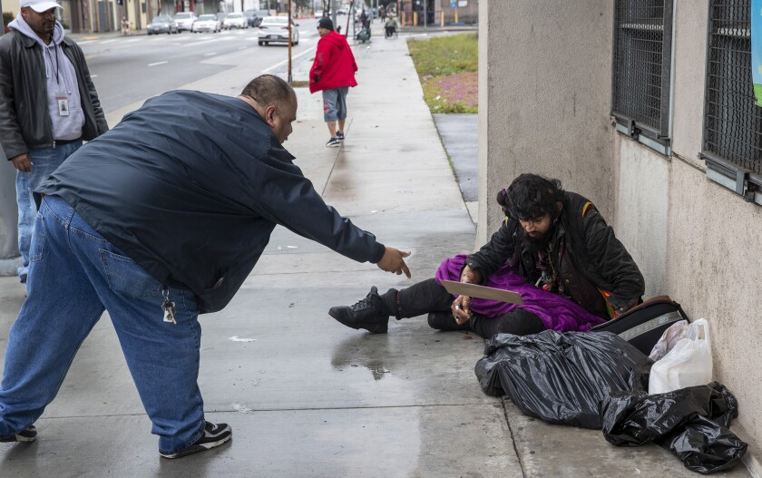 Outreach worker Ralph Gomez tosses a clipboard for a signature to homeless client Davis Soto during outreach in Los Angeles.