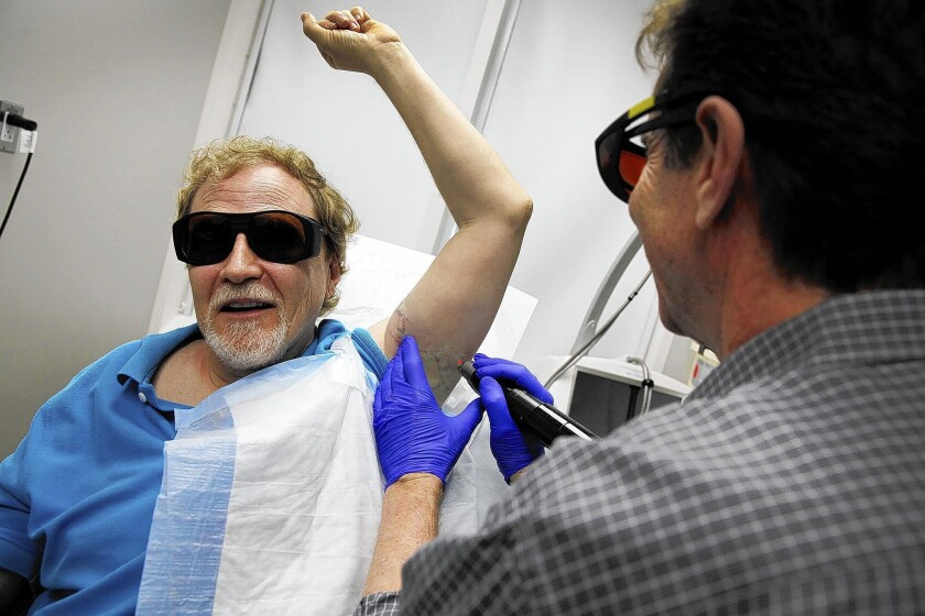 Wearing dark glass to protect their eyes, Dr. Gary Lask at UCLA uses a specialized laser to work on removing a tattoo from the arm of Stuart Yellen.