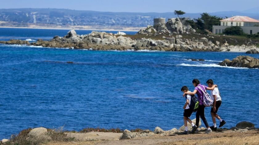 Tourists explore the rocky shoreline of Pacific Grove, a small town located on Monterey Bay.