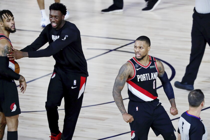 Portland Trail Blazers guard Damian Lillard (0) celebrates after their win over the Dallas Mavericks in an NBA basketball game Tuesday, Aug. 11, 2020, in Lake Buena Vista, Fla. (Kim Klement/Pool Photo via AP)