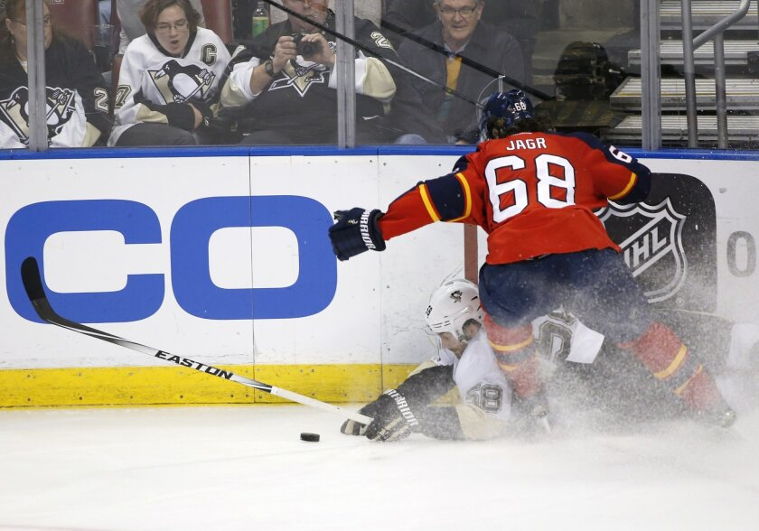 Pittsburgh Penguins defenseman Kris Letang (58) and Florida Panthers right wing Jaromir Jagr (68) battle for the puck during the second period of an NHL hockey game, Monday, Feb. 15, 2016 in Sunrise, Fla. (AP Photo/Wilfredo Lee)