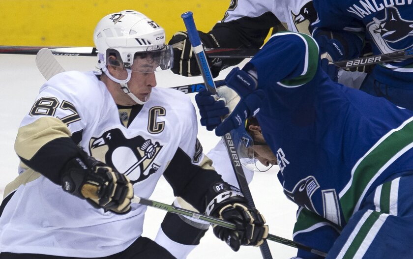 Pittsburgh Penguins center Sidney Crosby, left, vies for control of the puck with Vancouver Canucks center Brandon Sutter during the first period of an NHL hockey game Wednesday, Nov. 4, 2015, in Vancouver, British Columbia. (Jonathan Hayward/The Canadian Press via AP)