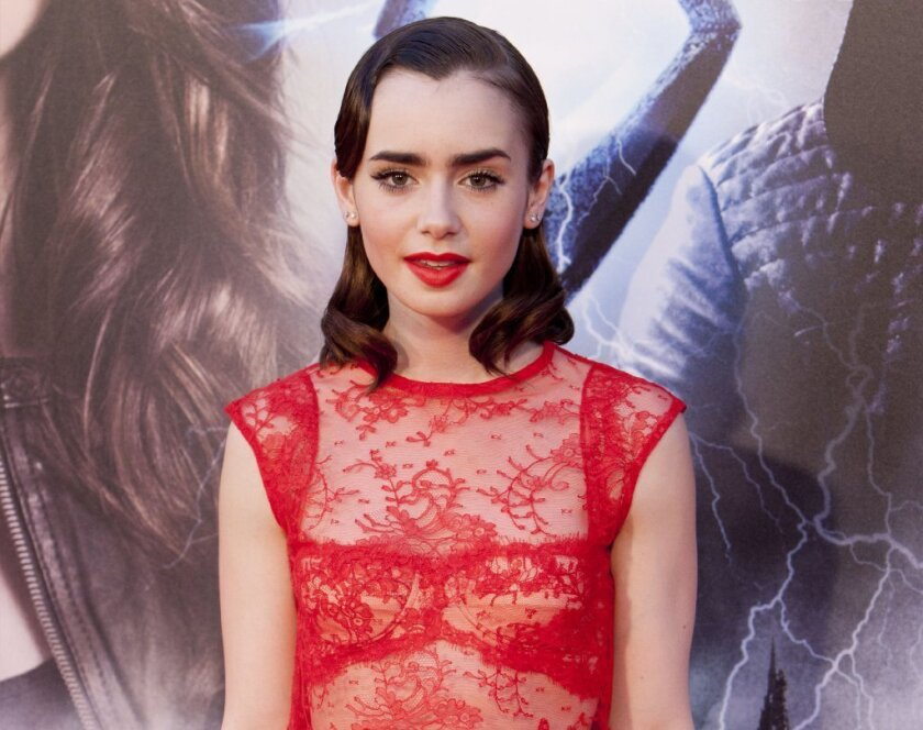 """English actress Lily Collins, shown at the premiere of the film """"The Mortal Instruments: City of Bones,"""" leads McAfee's list of """"most dangerous"""" cyber celebrities -- figures whose popularity is used by hackers to trick fans into downloading malware."""
