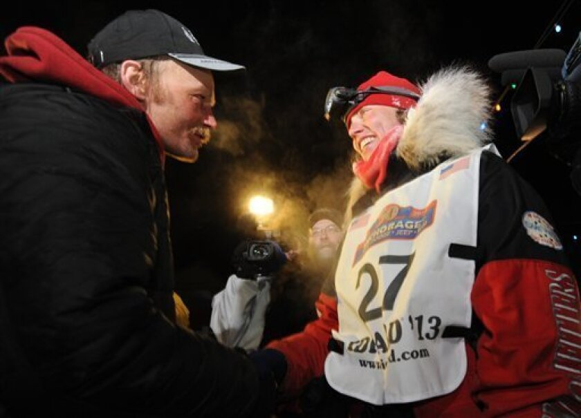 Mitch Seavey became the oldest winner and a two-time Iditarod champion when he drove his dog team under the burled arch in Nome on Tuesday evening, March 12, 2013.  He congratulates second place finisher Aliy Zirkle after she arrived in Nome. (AP Photo/The Anchorage Daily News, Bill Roth)  LOCAL TV