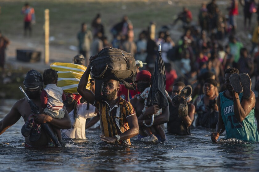 Migrants, many from Haiti, wade across the Rio Grande river from Del Rio, Texas, to return to Ciudad Acuña, Mexico, Monday, Sept. 20, 2021, to avoid deportation from the U.S. The U.S. is flying Haitians camped in a Texas border town back to their homeland and blocking others from crossing the border from Mexico. (AP Photo/Felix Marquez)