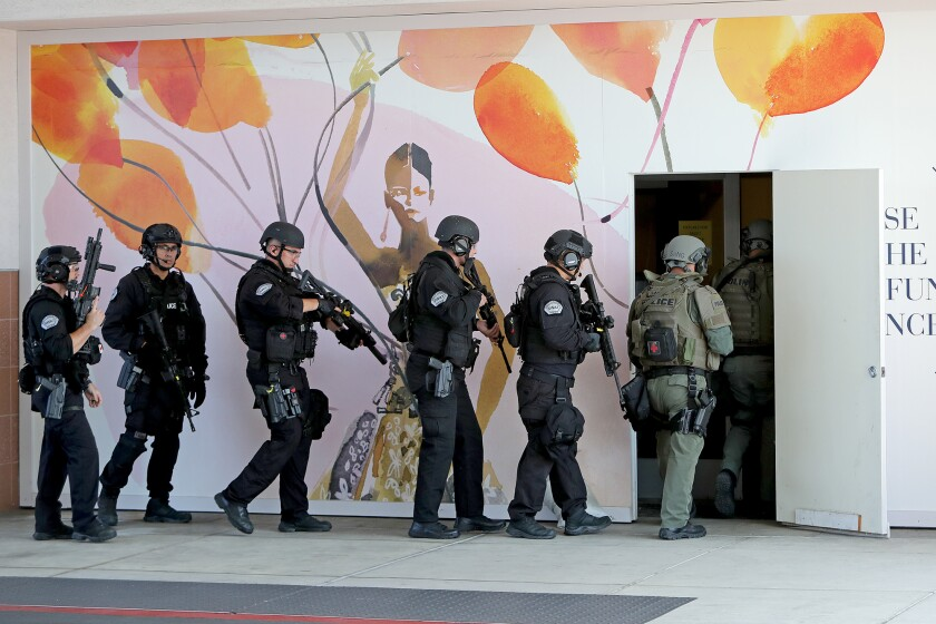 SWAT team members enter the former Sears building during a training exercise on Thursday at South Coast Plaza.