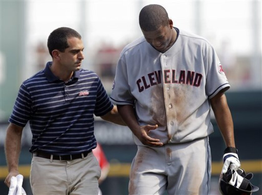 Trainer Lonnie Soloff, left, helps Cleveland Indians starting pitcher Fausto Carmona walk off the field with an undisclosed injury during the third inning of an interleague baseball game against the Cincinnati Reds, Saturday, July 2, 2011, in Cincinnati. (AP Photo/Al Behrman)