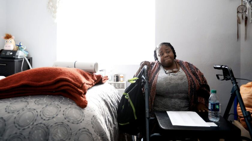 Natalie Purnell sits in her room at a former motel that is temporarily being used to house homeless
