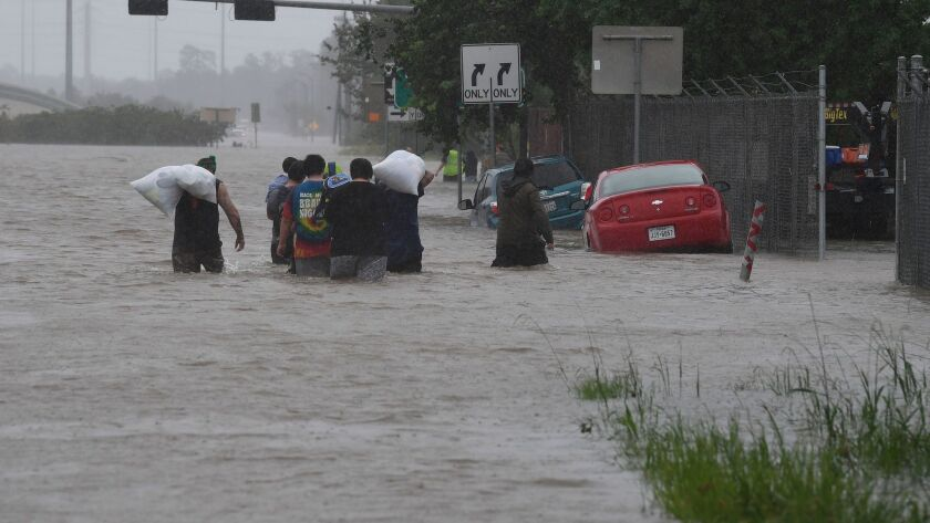 Evacuees wade through a flooded Highway 90 after fleeing their homes in Houston on Monday.